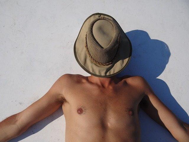 homme qui bronze au soleil, se protège avec un chapeau